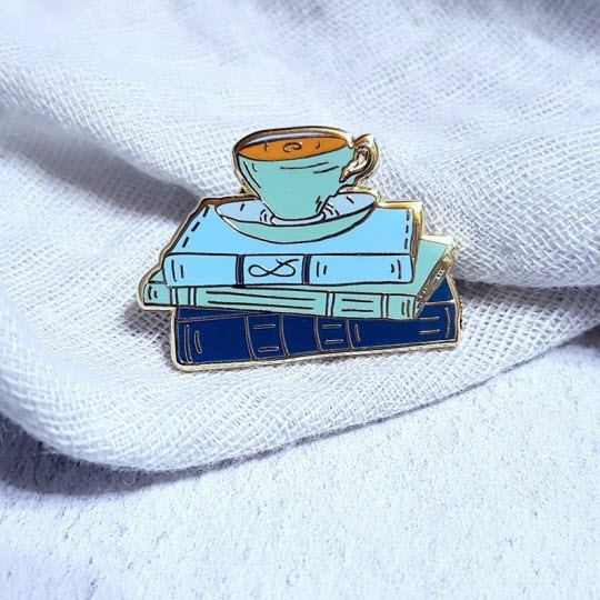 Pin: Tea cup and a stack of blue books