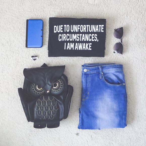 Casual outfit with graphic tee, jeans, sunglasses, enamel pin, and fashion backpack