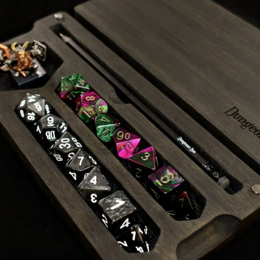 Photo featuring a wooden box with compartments for D&D dice, a figurine, and a pencil.