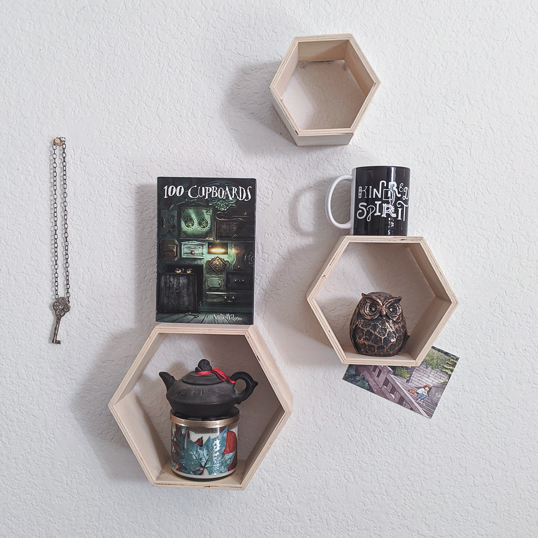 Bookstagram photo features three hexagon shelves arrayed with an assortment of items, including a KINDRED SPIRIT mug from BumbleBess.com, a tiny teapot balanced atop a candle, a postcard with art from Heikala, a pendant with a silver skeleton key, and the book 100 Cupboards by N. D. Wilson.