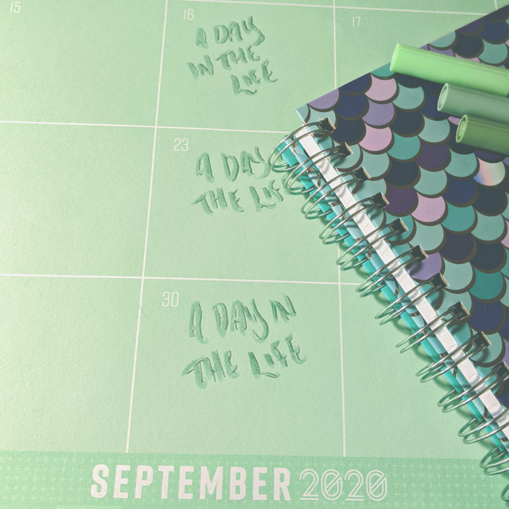 A photograph with a desk calendar for September 2020, matching notebook, and colorful markers