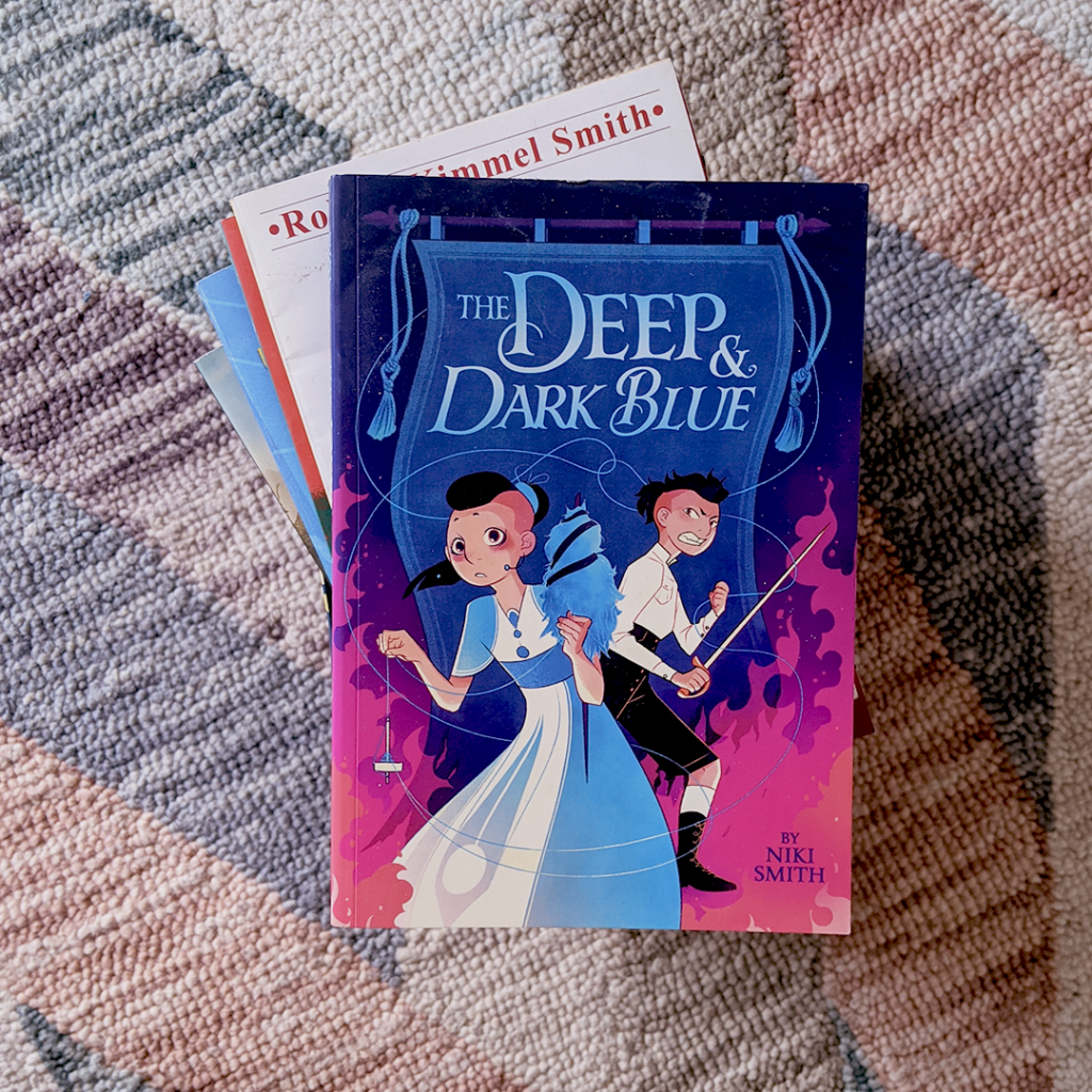 Photograph features the book THE DEEP AND DARK BLUE by Niki Smith
