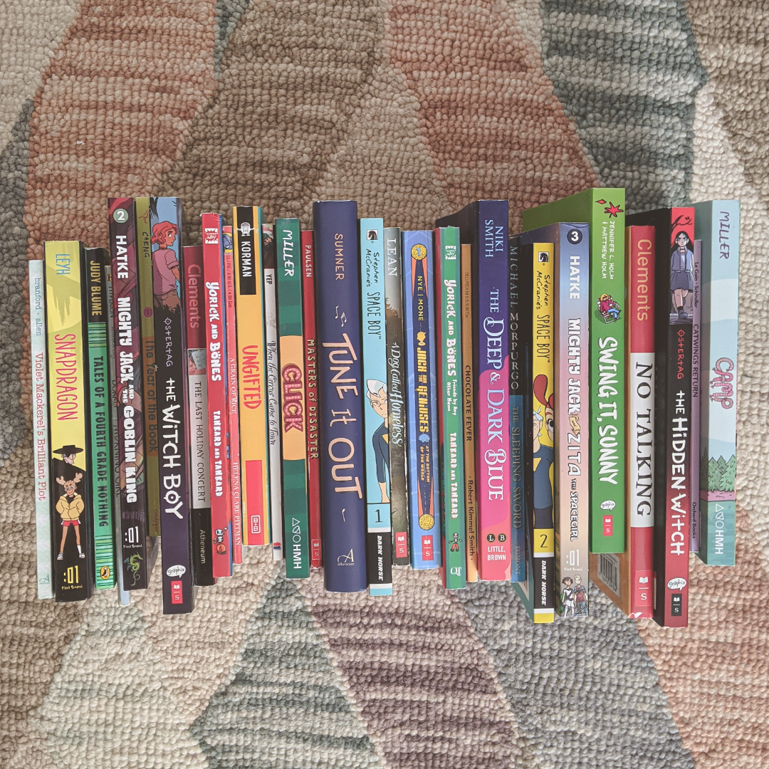 Photograph of a stack of Middle Grade books standing spine-up on a rug.